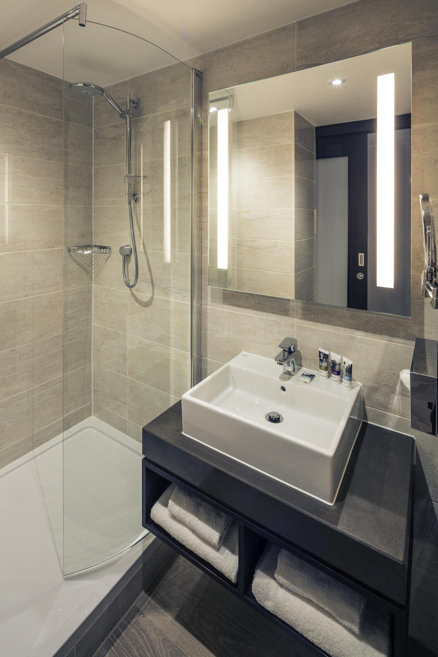 Modern shower room themed in gray with rectangle sink with travel size shampoo and conditioner, white towels.