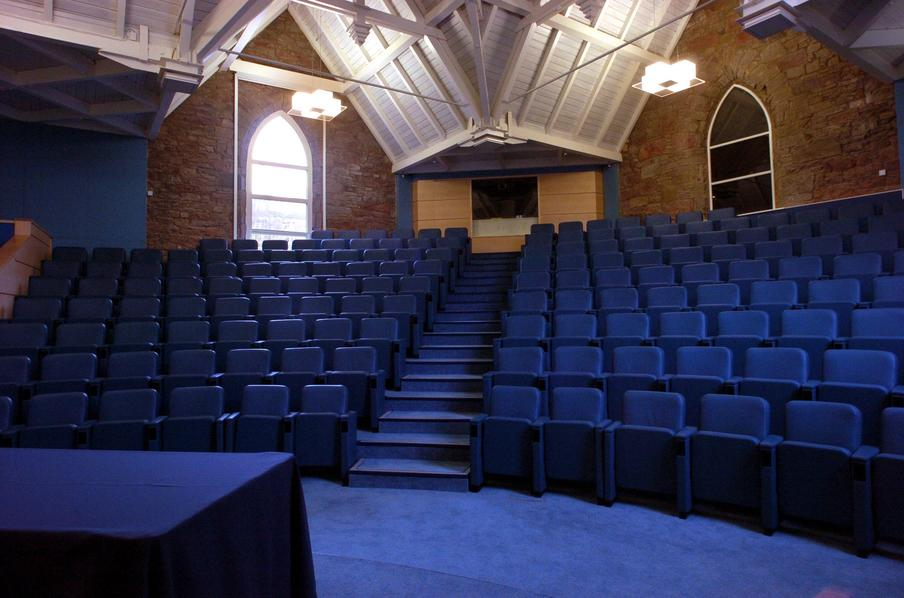 Tiered auditorium  with wooden vaulted ceiling and arched windows and blue colour theme.