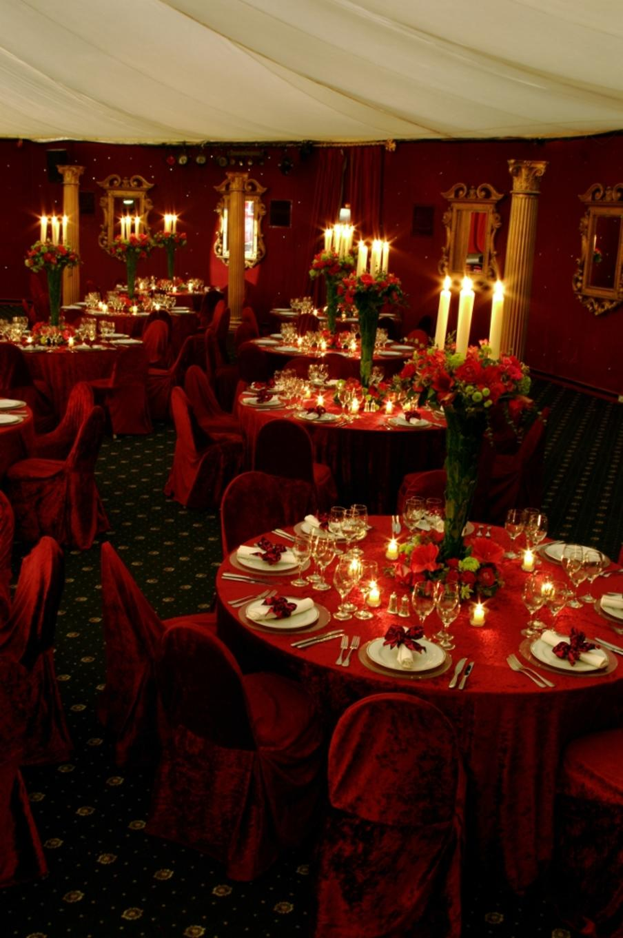 A red theme for dinner set on round tables with large centerpiece floral and candle decoration on each table