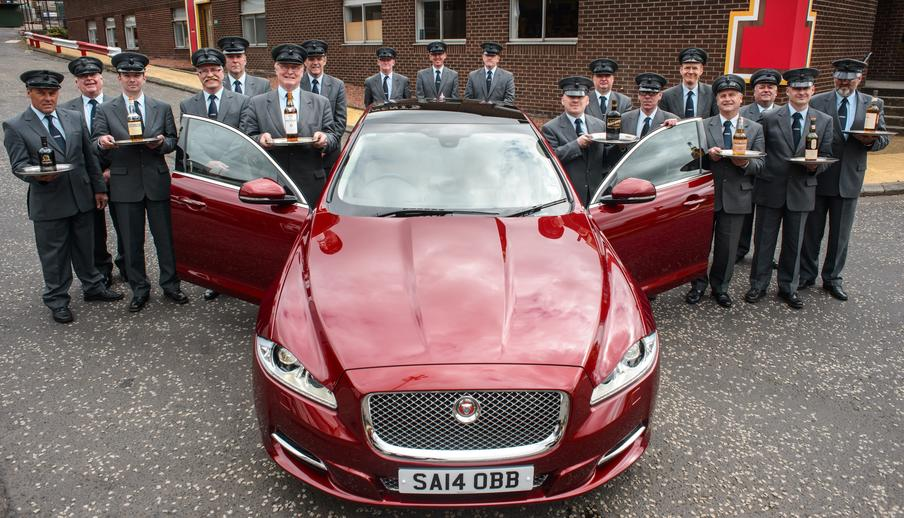 Little's team of fully uniformed chauffeurs gather around one of our Jaguar XJL's after a full day of training at the Tennents Brewery in Glasgow.