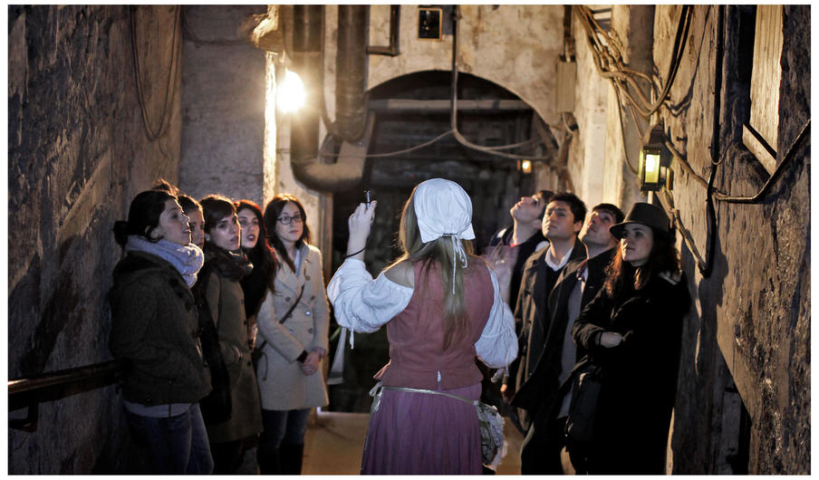 Period character leads members for the tour down into the street with atmospheric lighting