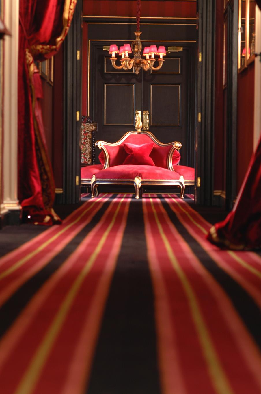 Looking down the hotel corridor to a feature seating area within the reception of the hotel with striped carped with red, black and gold theming