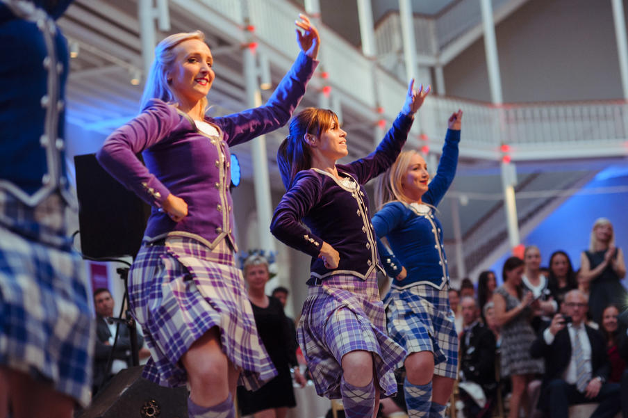 Traditional Highland dancers performing for a corporate crowd at the National Museum of Scotland