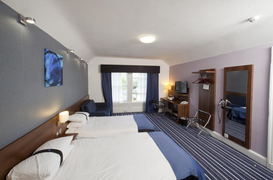 Large room with twin double beds, blue colour theme with large windows, desk and luggage rack.