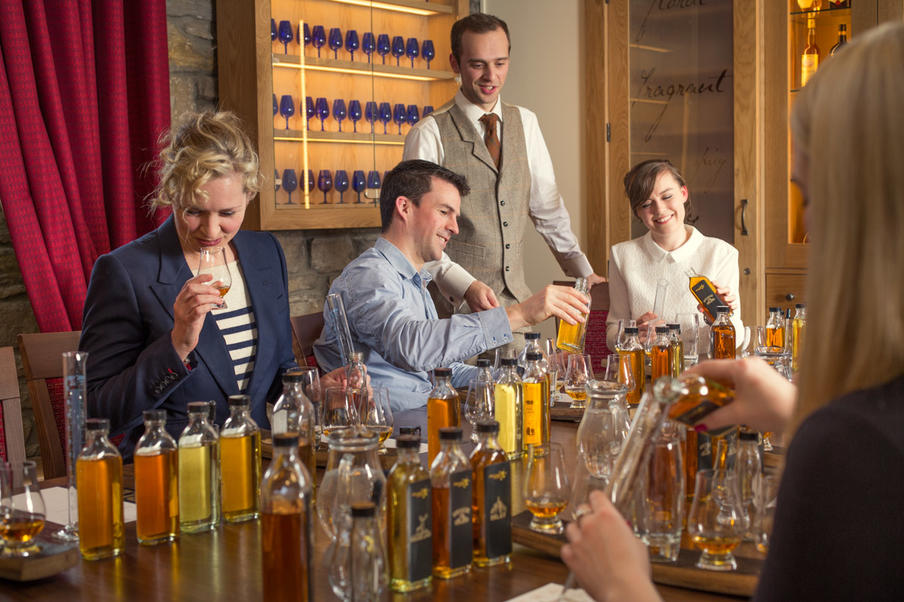 A group of people participating in a fun and educational blend your own whisky experience with a tutor.