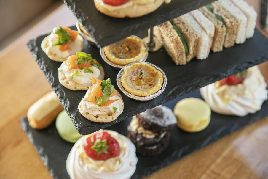 A cakestand displaying blinis, mini quiches, sandwiches and cakes